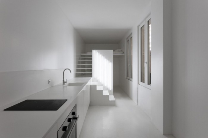 Small-White-One-Room-Apartment-with-White-Kitchen-Counter-and-White-Stairs-to-Access-Bedroom-Loft-Area-936x623